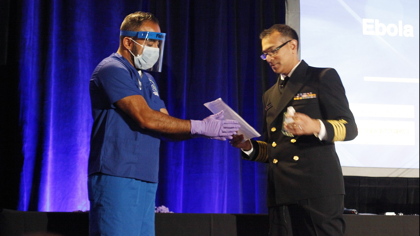 Two health care workers showing protective gear (gloves, mask, face shield)