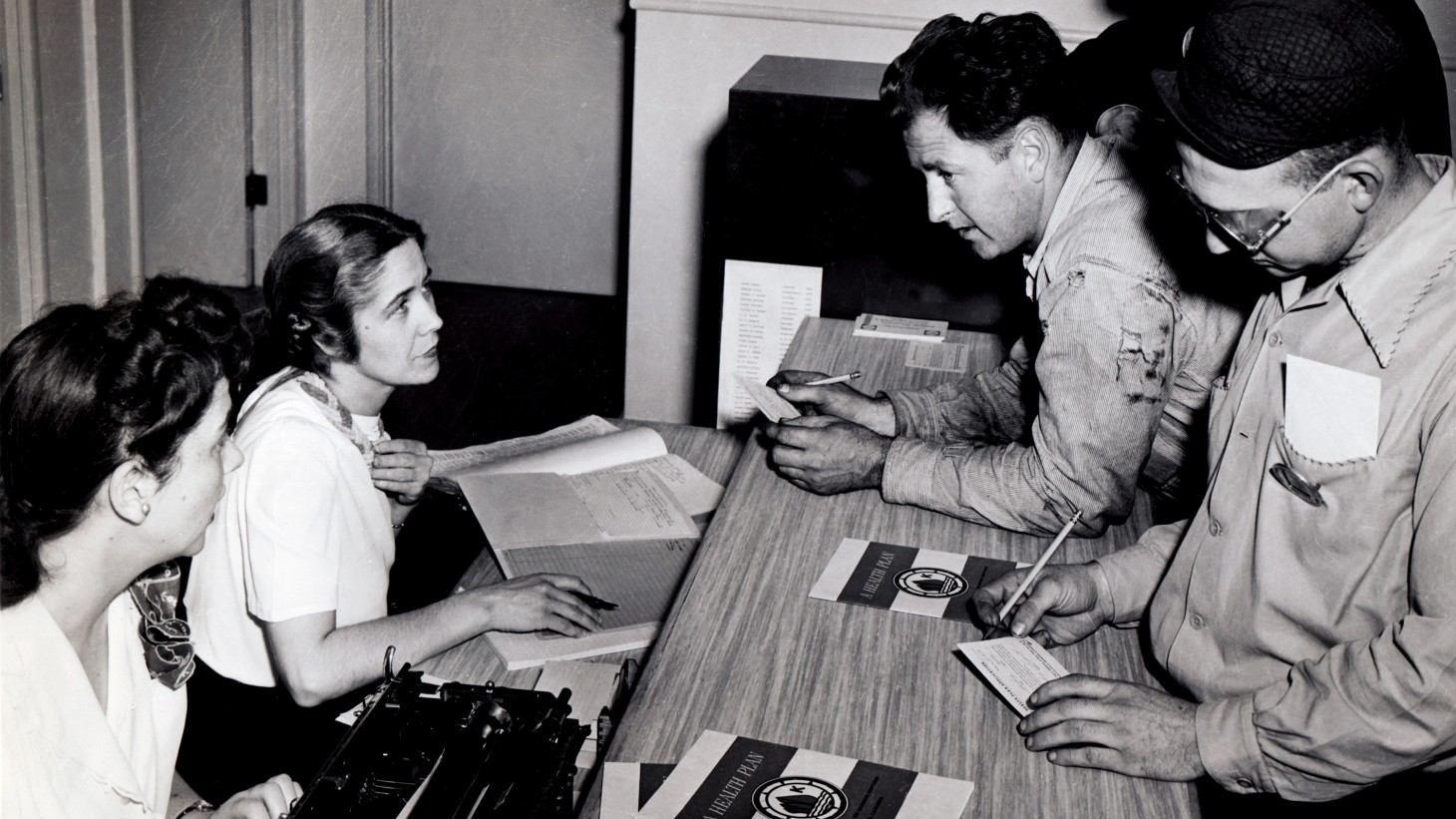 Shipyard workers in 1942 signing up for health care coverage
