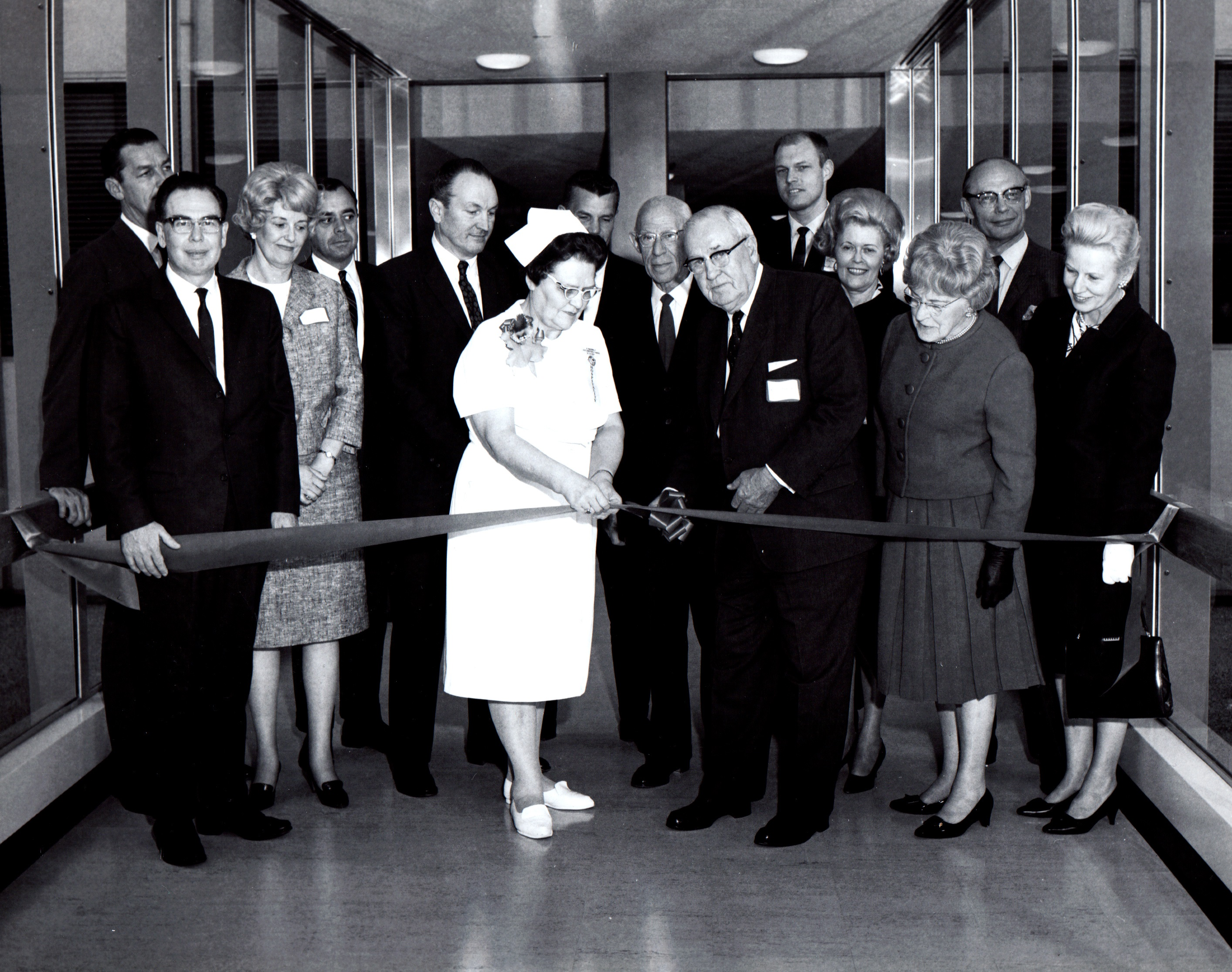 A nurse and group of dignitaries at a ribbon cutting