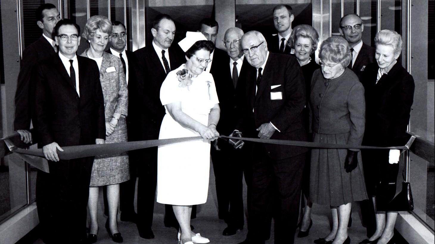 A nurse and group of dignitaries at a ribbon cutting