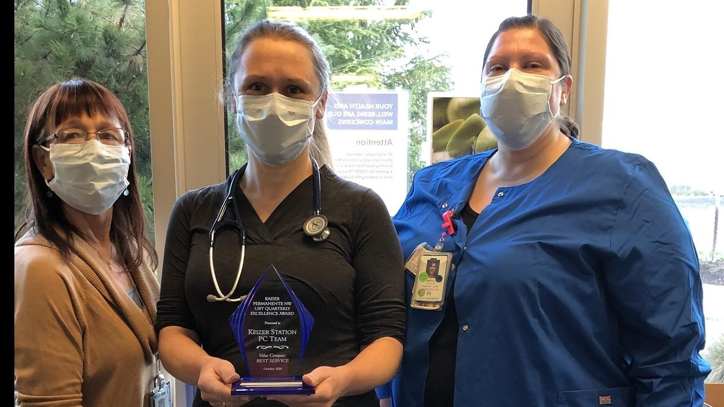 3 women, wearing mask, posing with an award