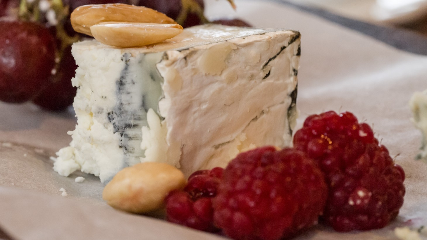 hunk of blue cheese with nuts and raspberries