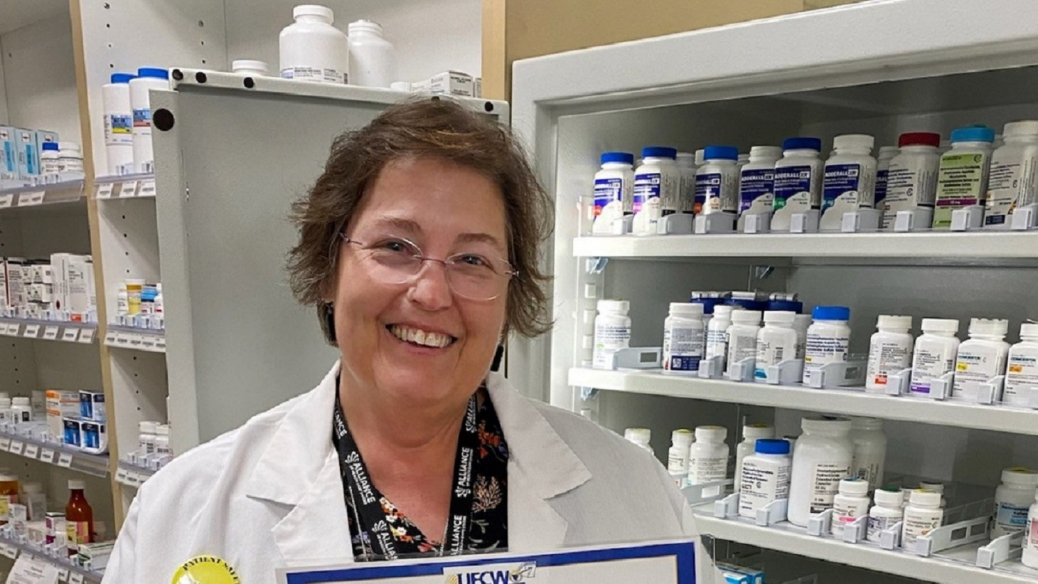 woman in lab coat posing in front of shelves of pill bottles