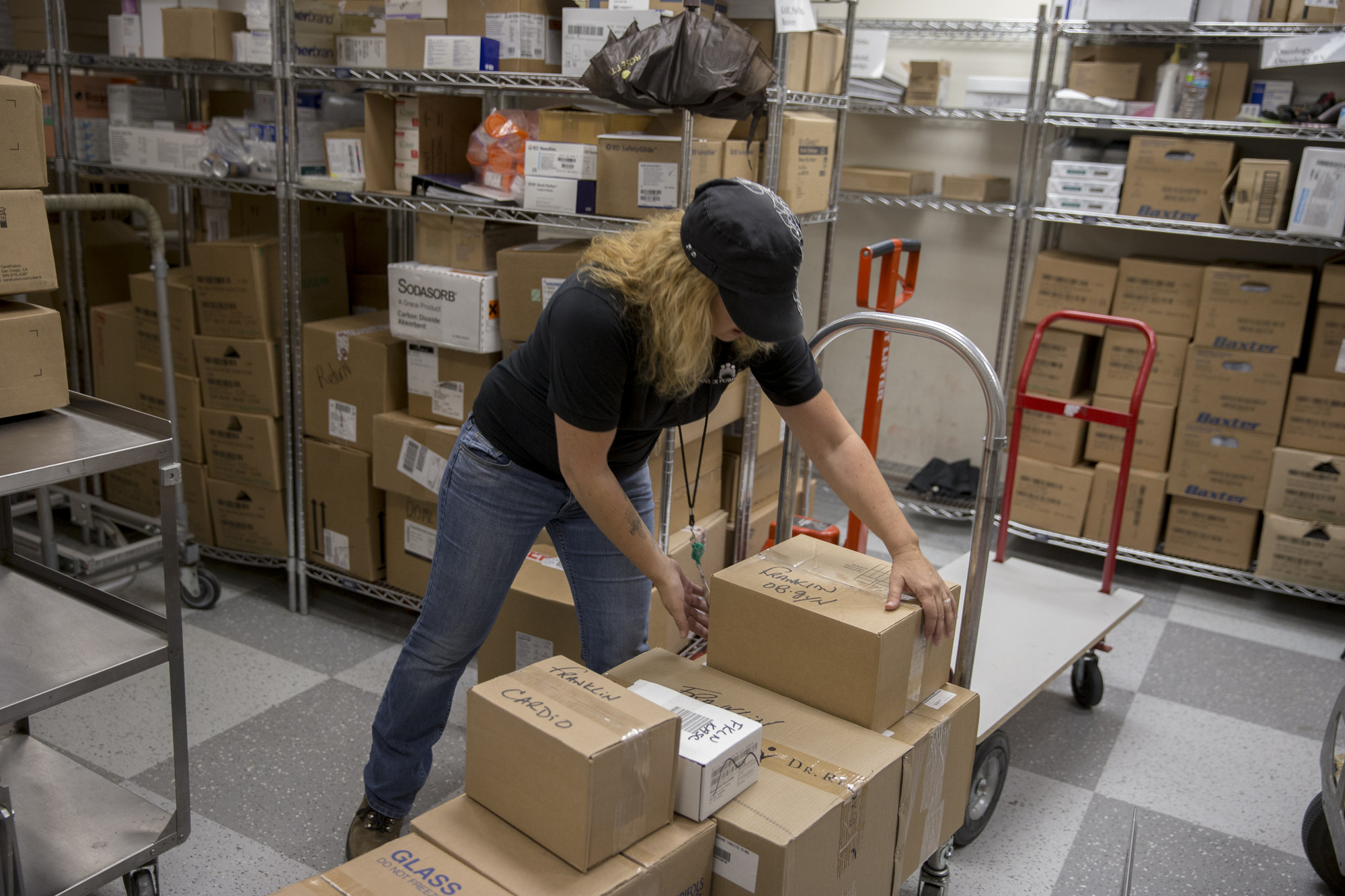 A mail services worker unloads packages