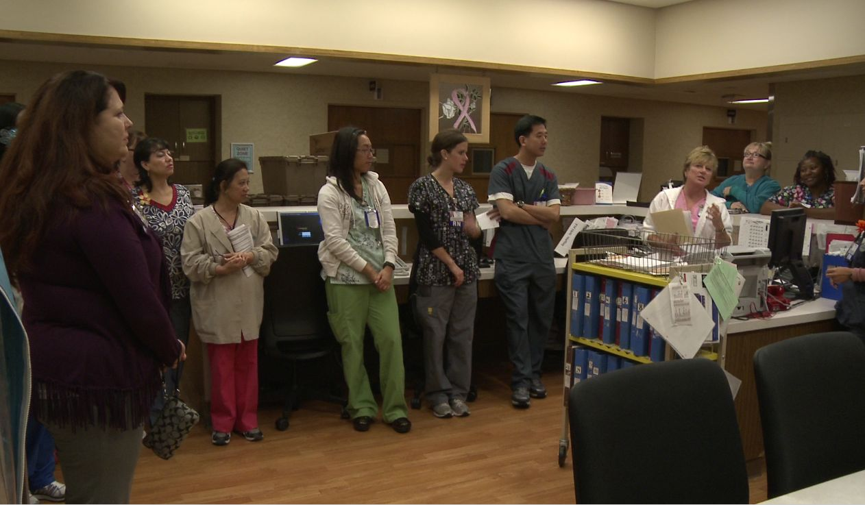 Members of a health care team huddle at the nurses' station