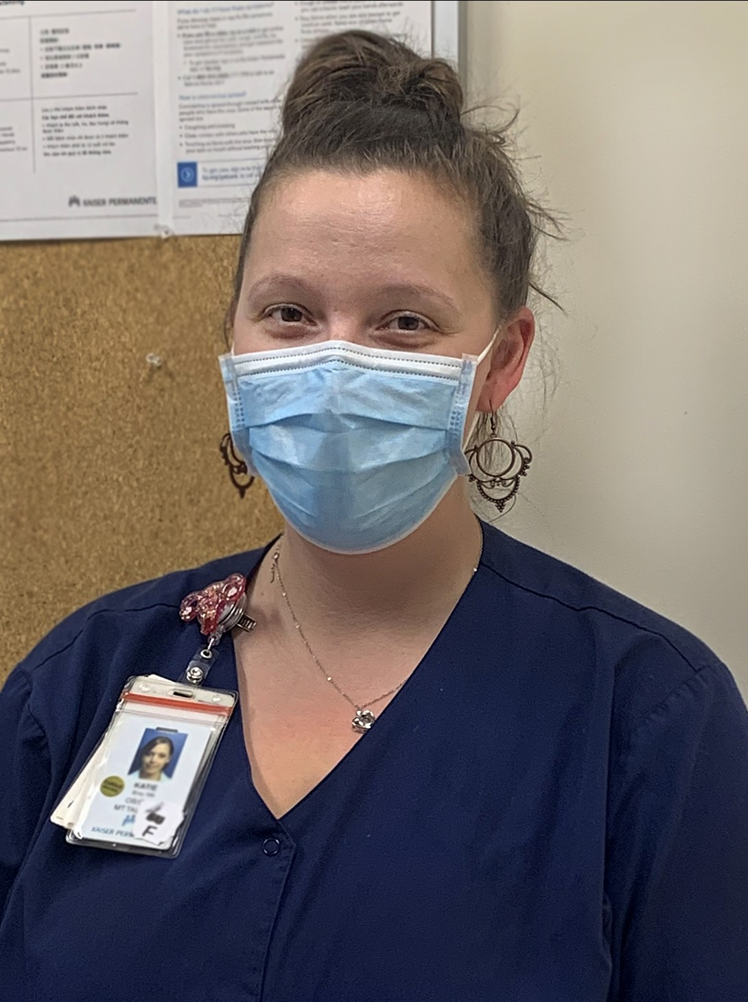 A female health care worker, wearing dark blue scrubs and a light blue mask