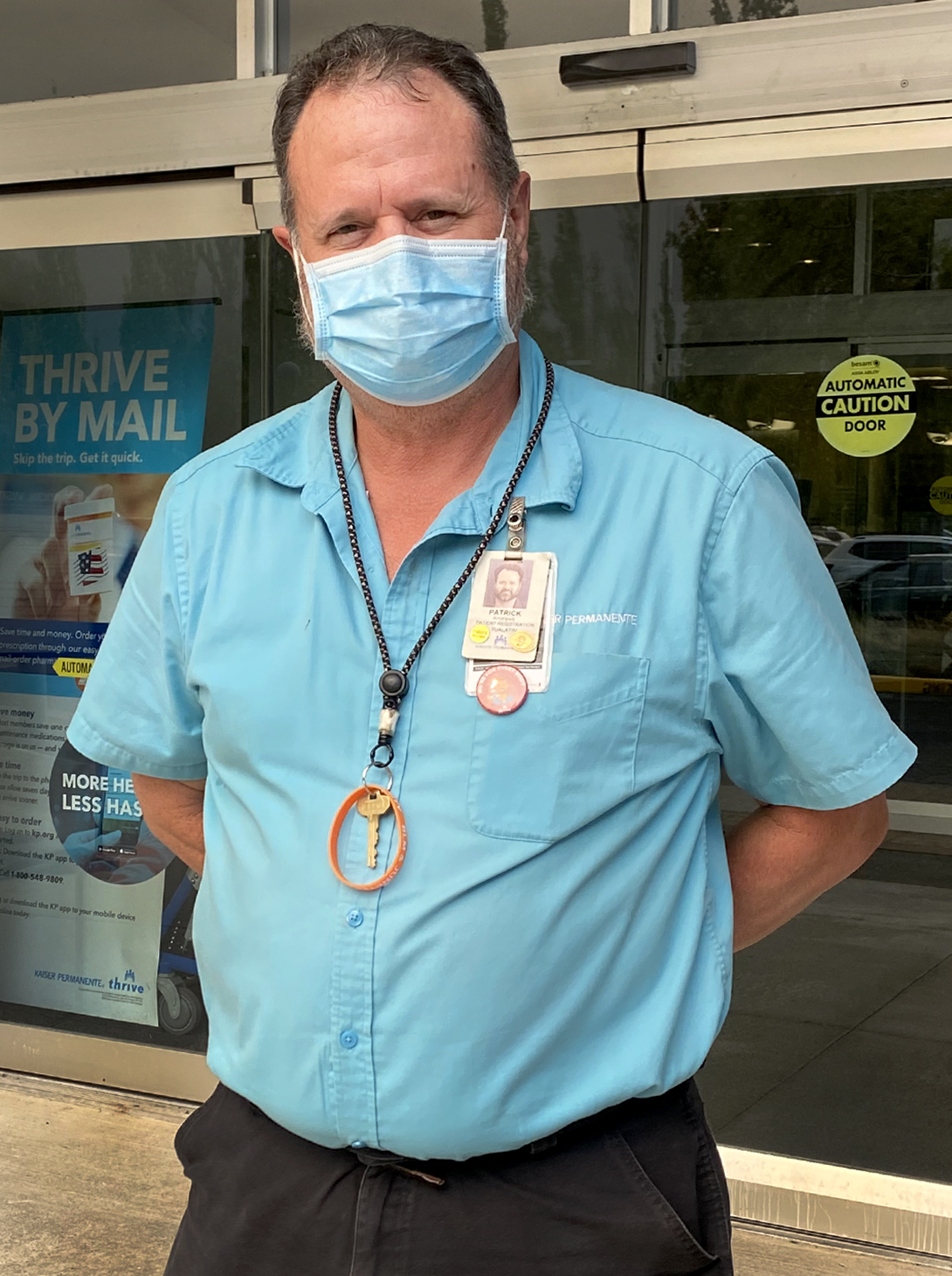 Portrait of a man, wearing a teal shirt and a mask