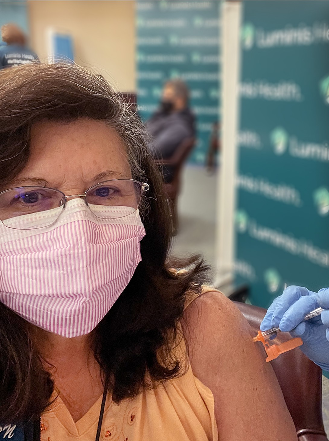 Woman with brown hair wearing glasses and a shirt receiving the covid vaccine.