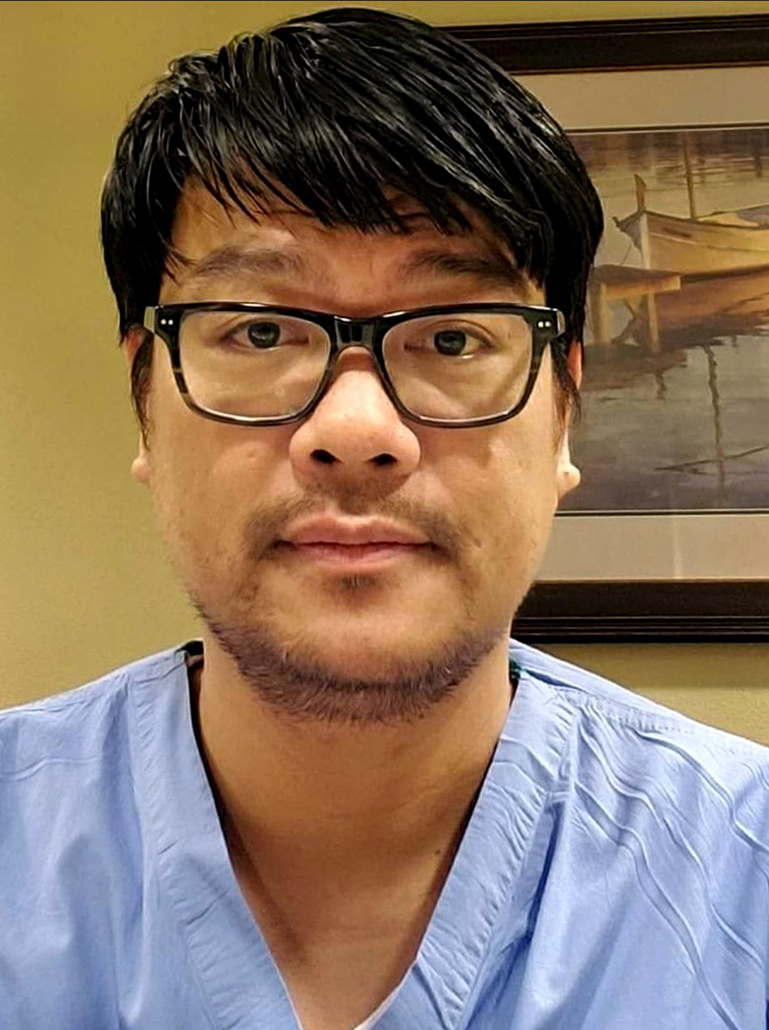 Asian male with black hair wearing glasses and blue scrubs