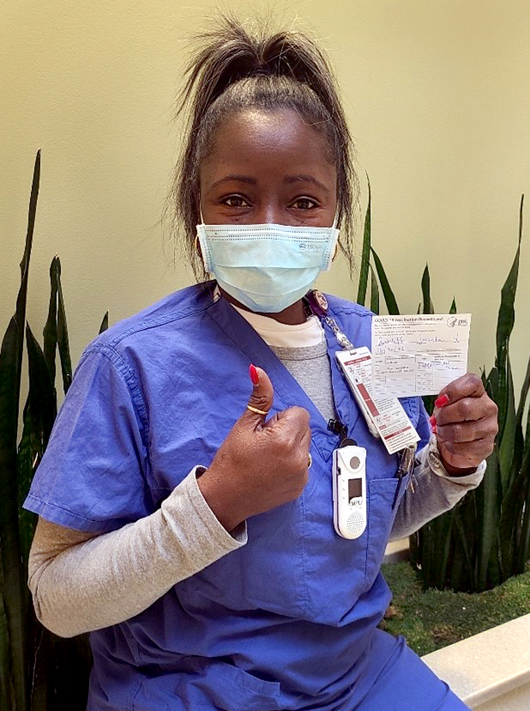 Black woman wearing blue scrubs, holding up her vaccination cards and giving the thumbs-up signal