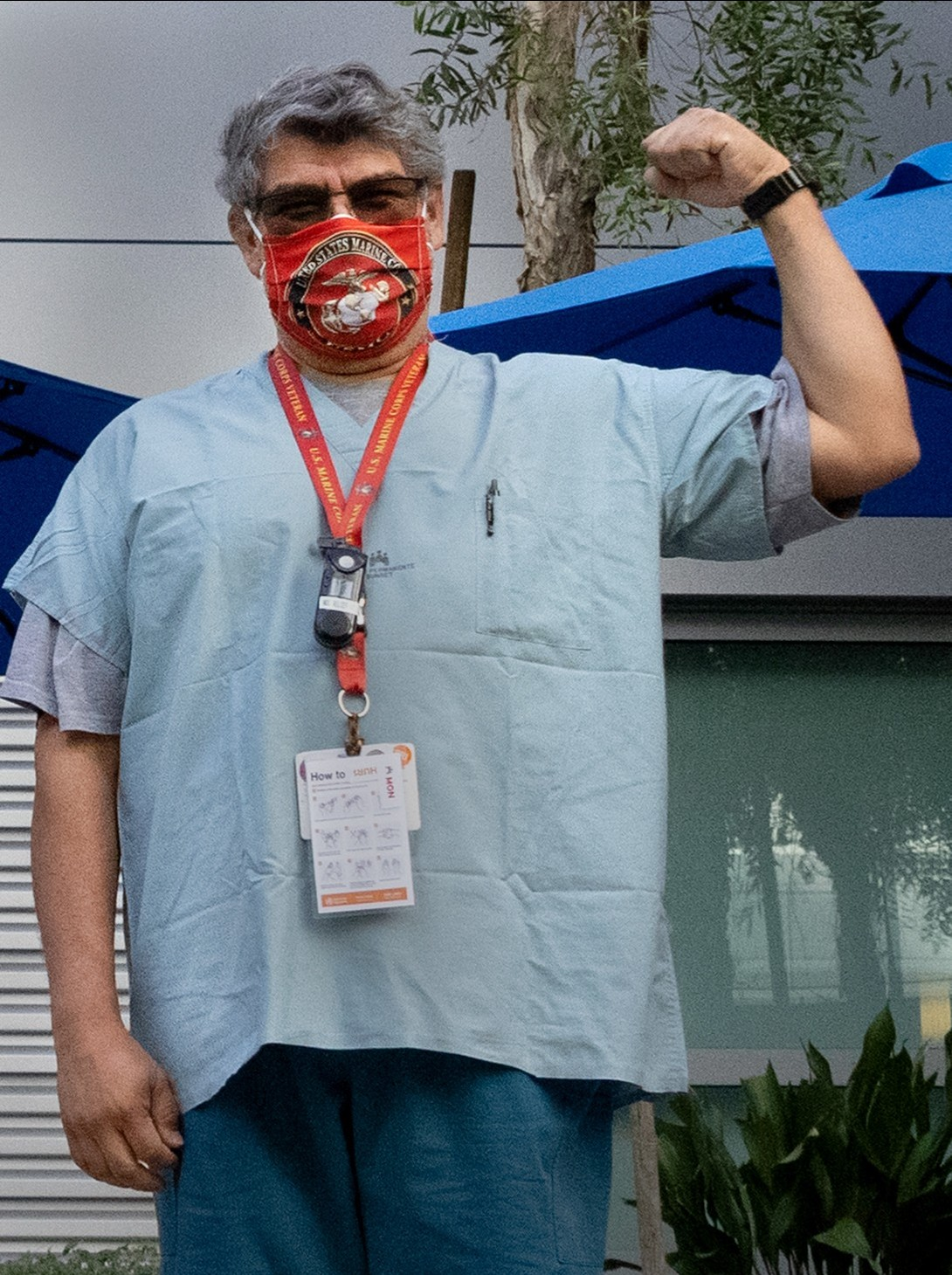 Man in scrubs, wearing a face mask, with left arm raised in a fist