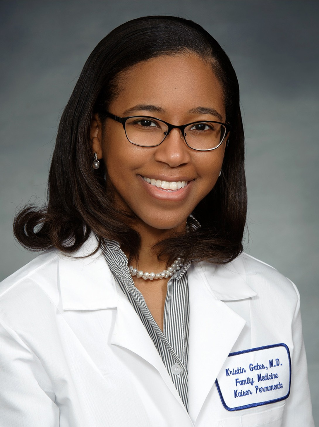 Portrait of a female African American doctor, wearing a white coat