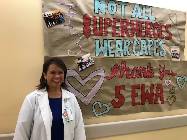 "Female health care manager wearing a white lab coat, standing in front of a banner that says, ""Not all superheros wear capes."""