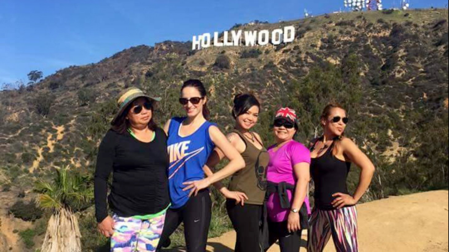 Team members pose with the Hollywood sign