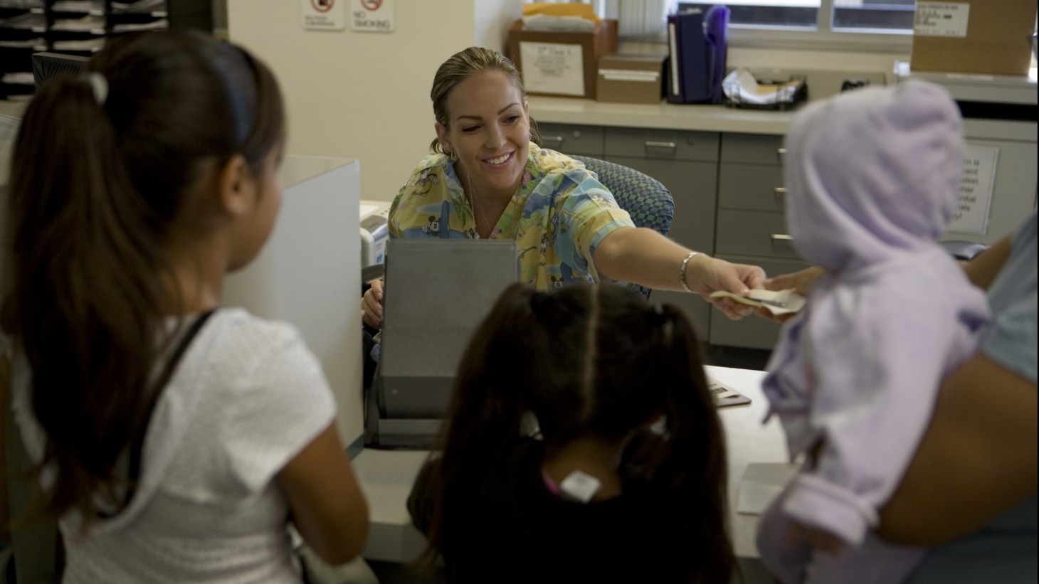 Receptionist welcoming three children to the clinic