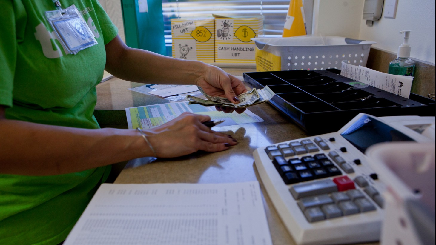 worker counting cash at a desk with a large calculator on it