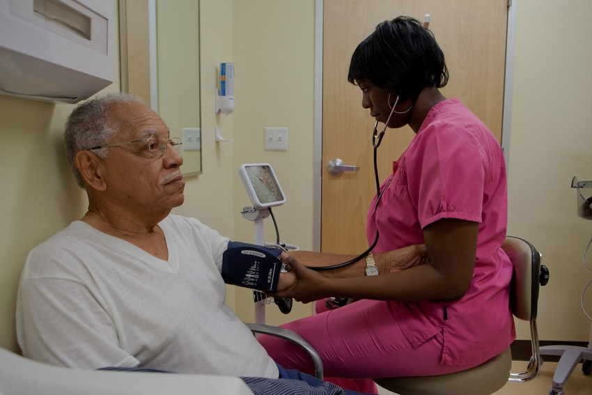 Nurse checking a elderly man's blood pressure