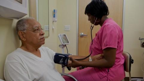 Nurse checking a elderly man's blood pressure