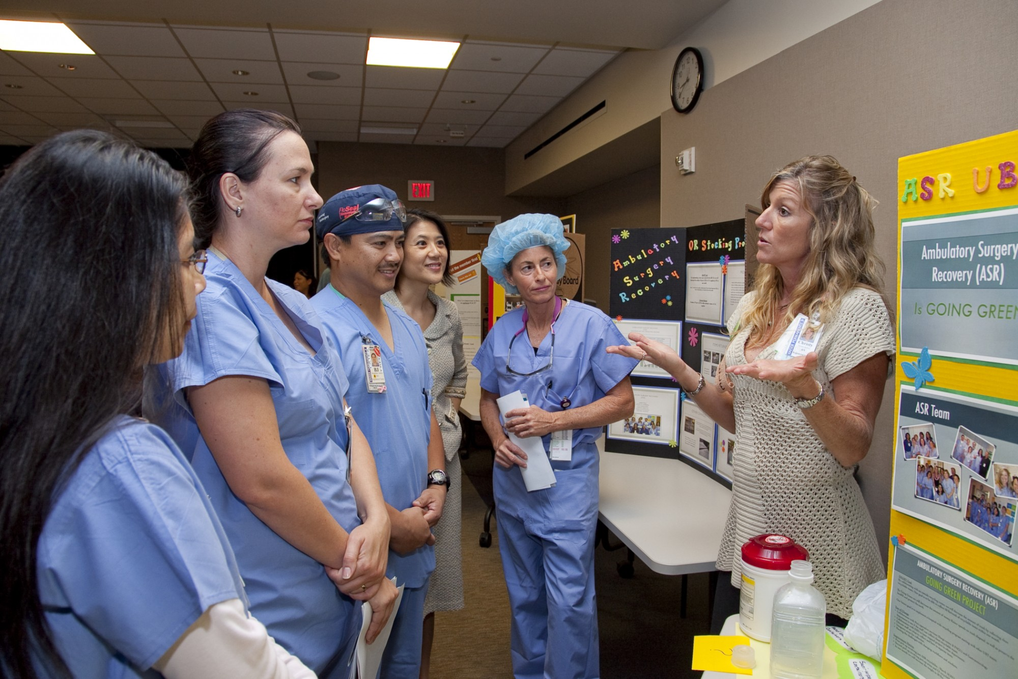 A woman explains a storyboard to several nurses gathered around her