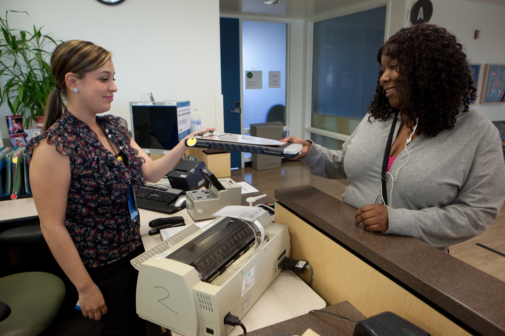 Receptionist greeting a patient at a clinic