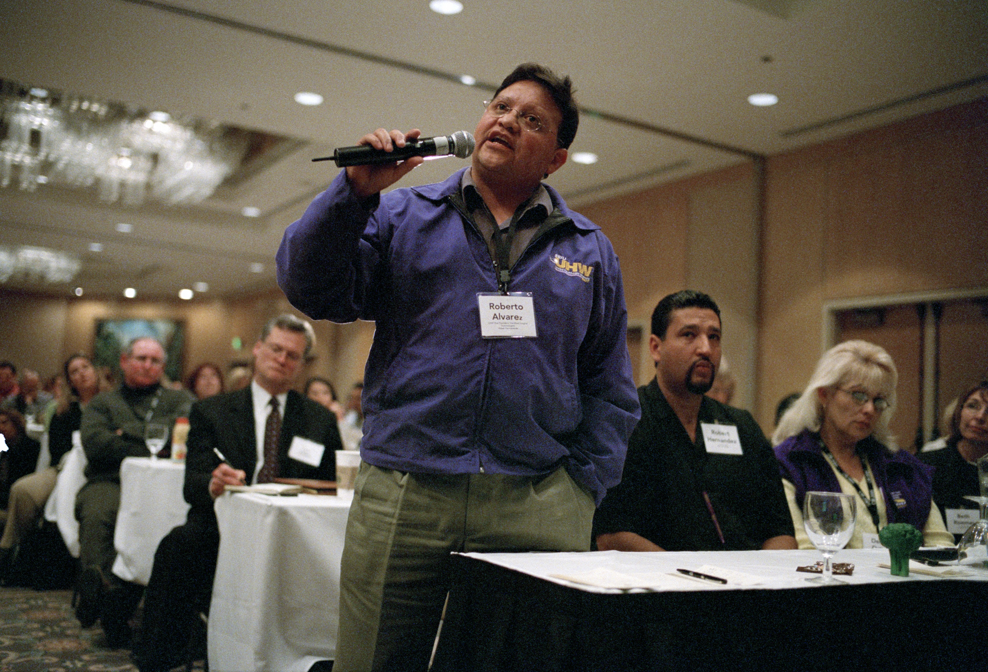 A UHW member (wearing purple jacket) speaks into a microphone