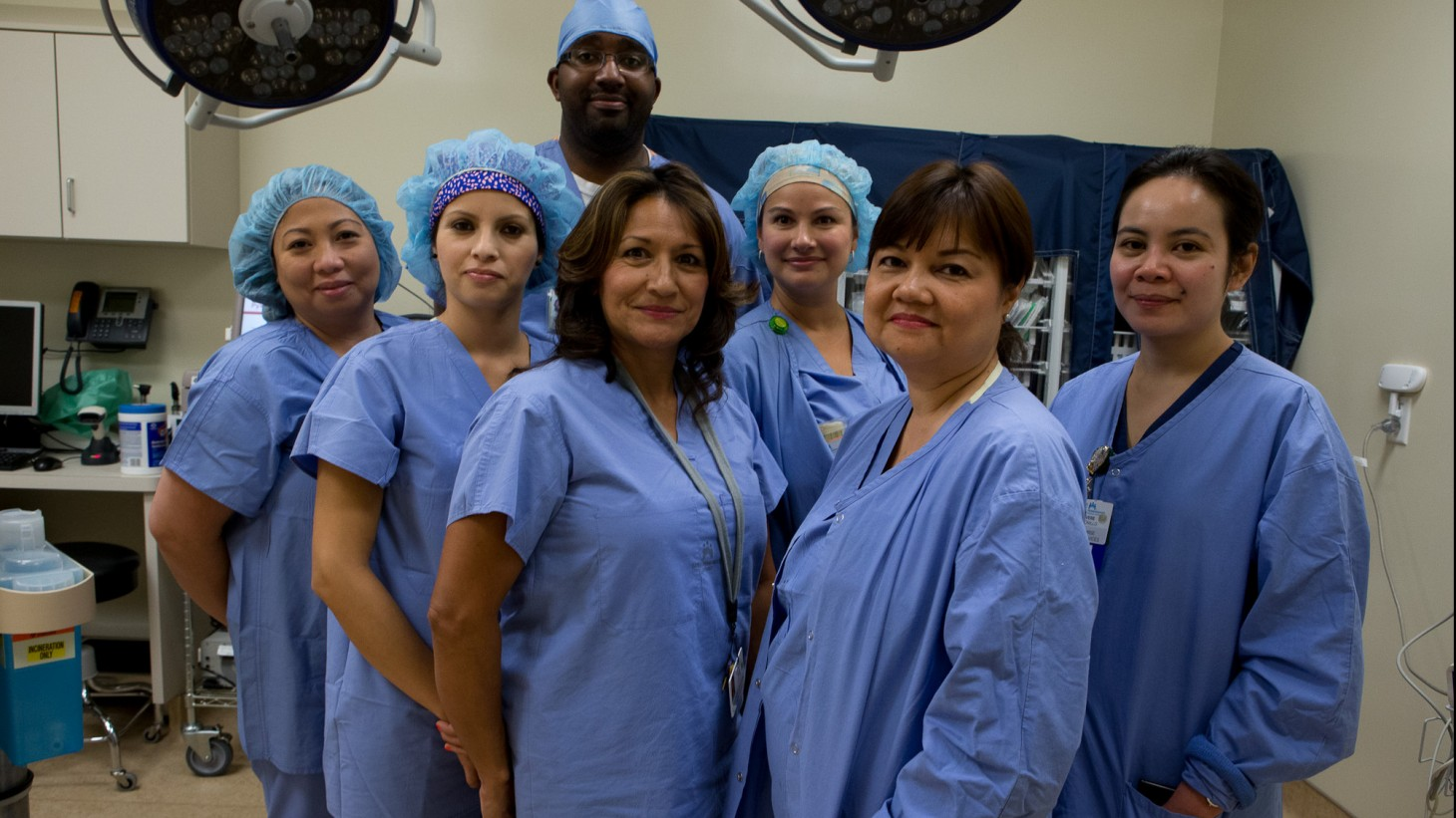 A diverse group of health care workers wearing blue scrubs