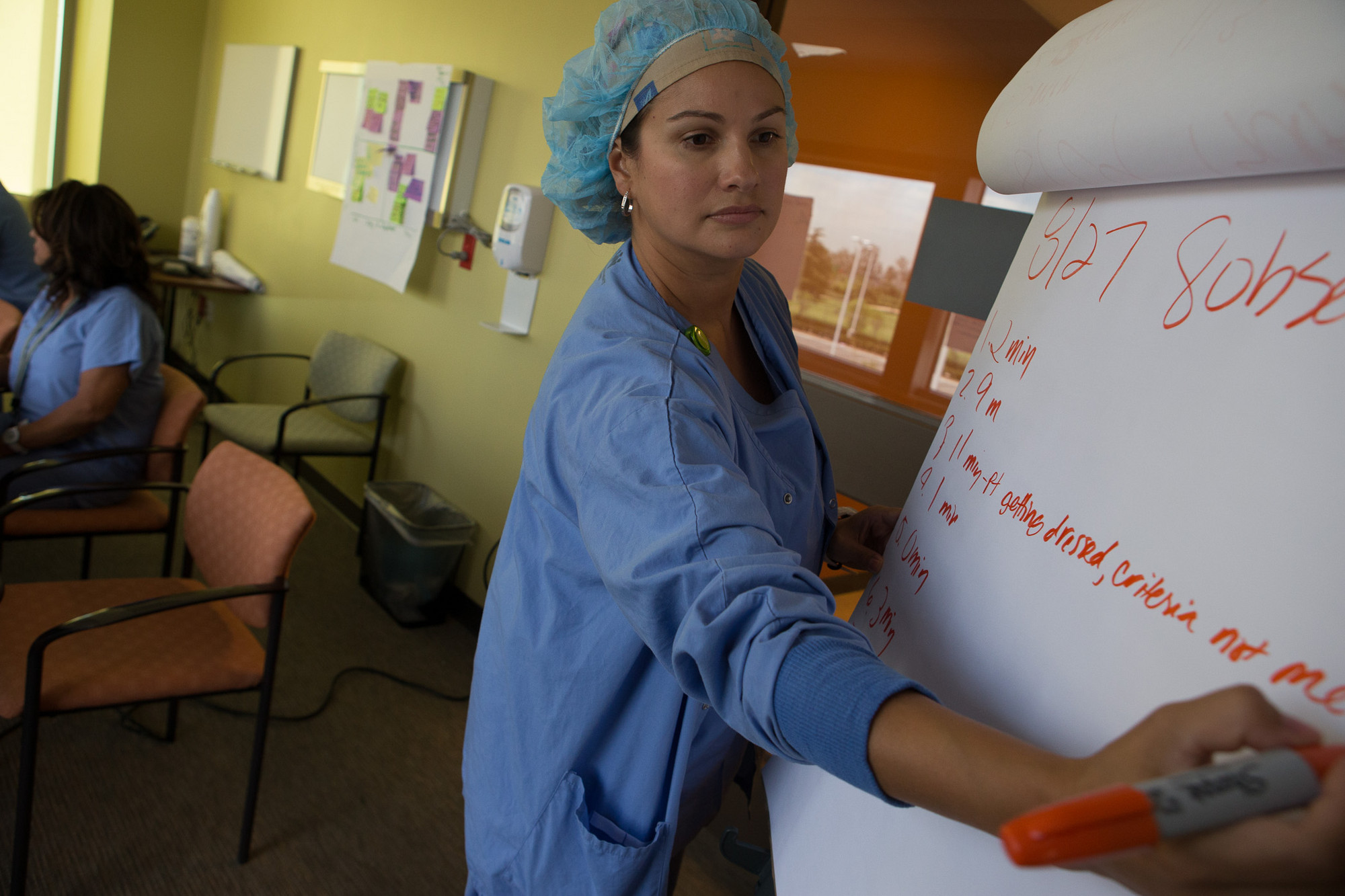 Health care worker in blue hairnet writing on a flip chart