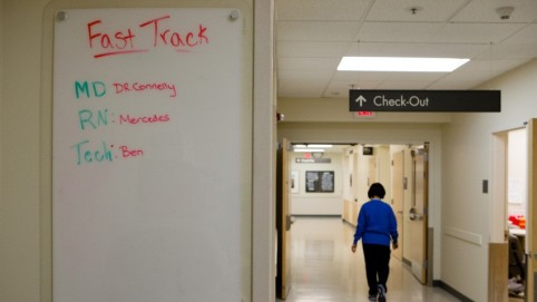 """White board reading """"fast track"""" and person walking under a sign that says """"check out"""""""
