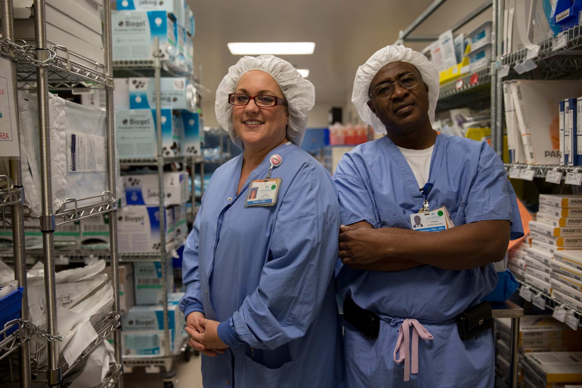 Two health care workers, wearing blue scrubs and white hair coverings, in a supply closet