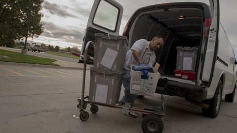 Courier loading the back of a van with packages