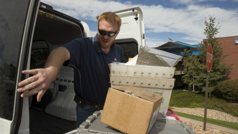 Courier taking packages out of the back of his van
