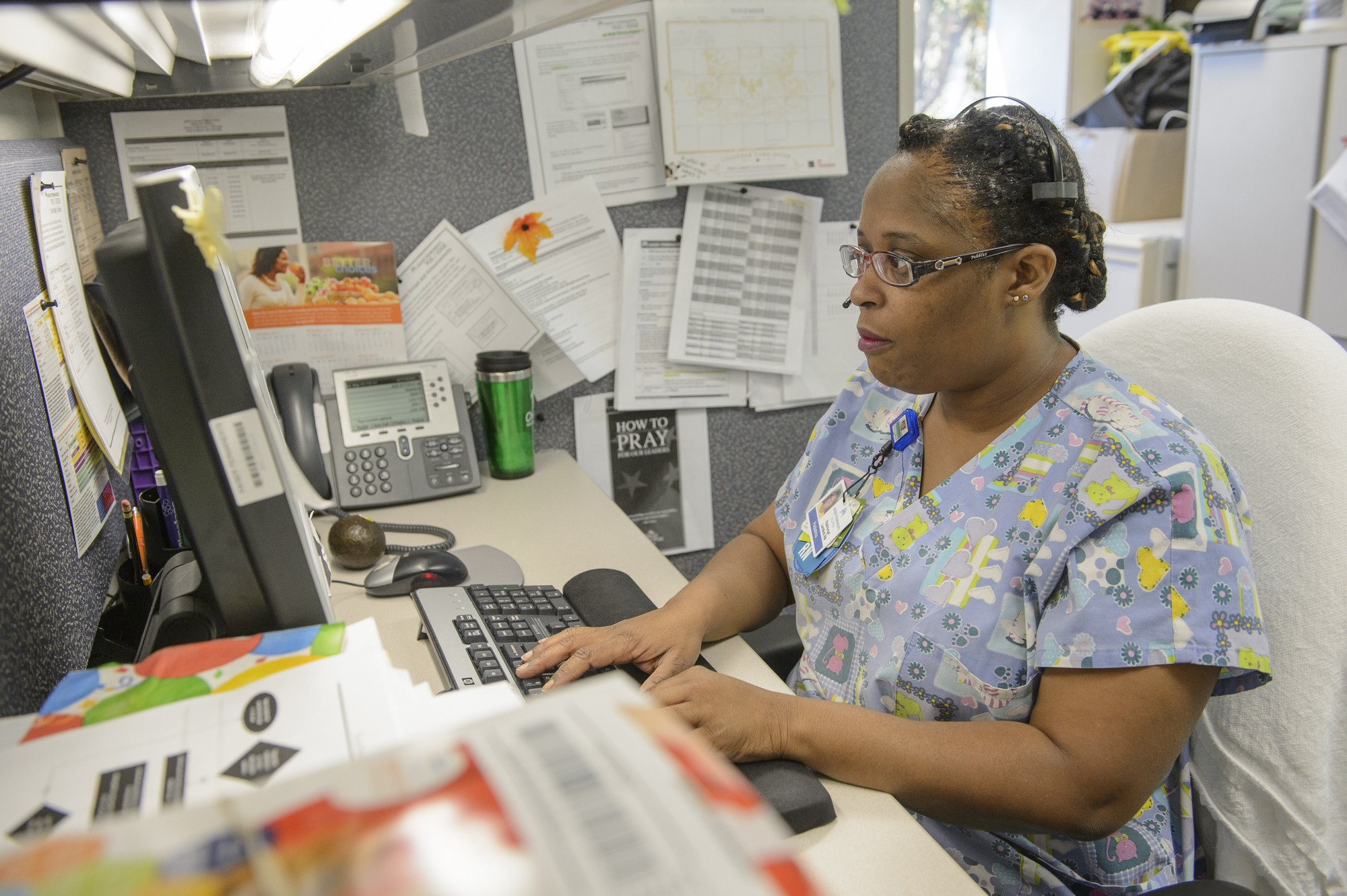 Nurse typing and looking at a computer screen