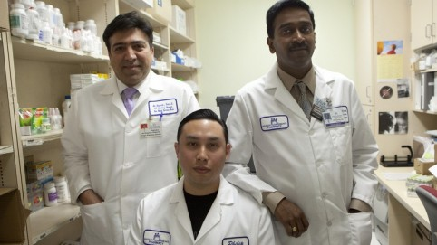 Three male pharmacy workers posing in their white lab coats