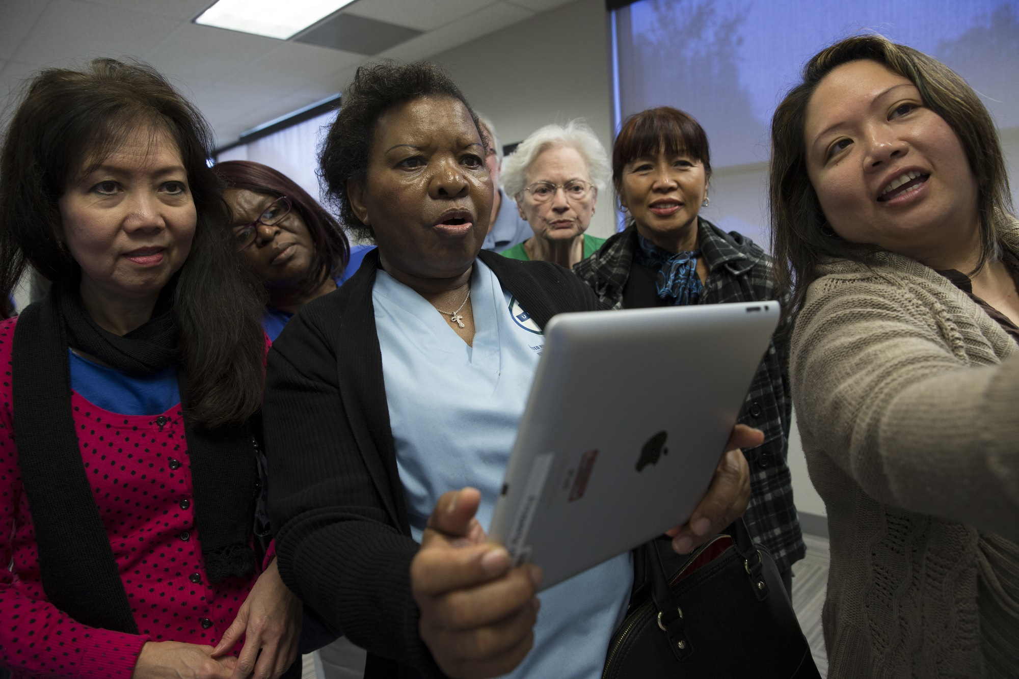 women looking in awe at an iPad