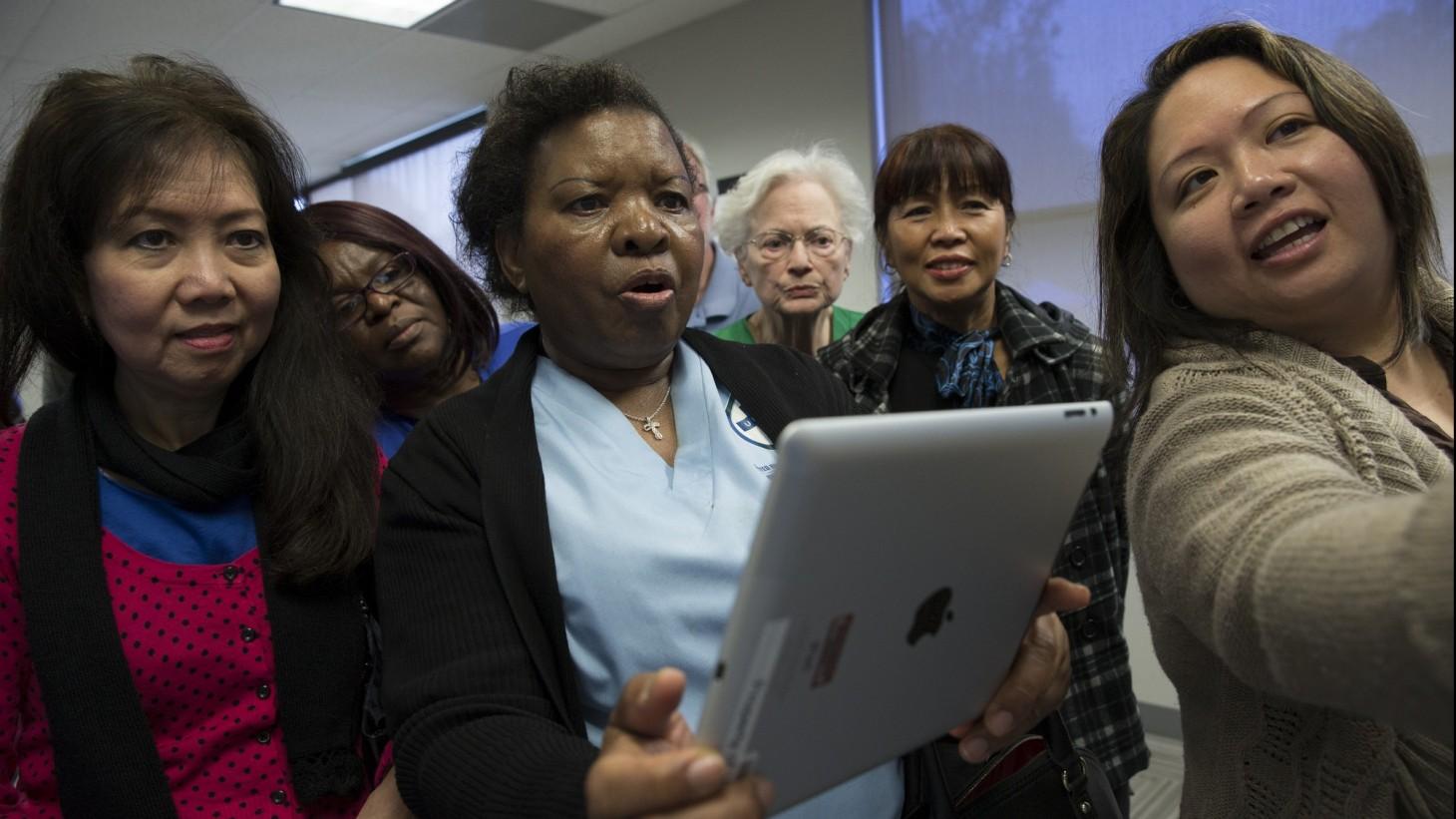 women looking in awe at an iPad