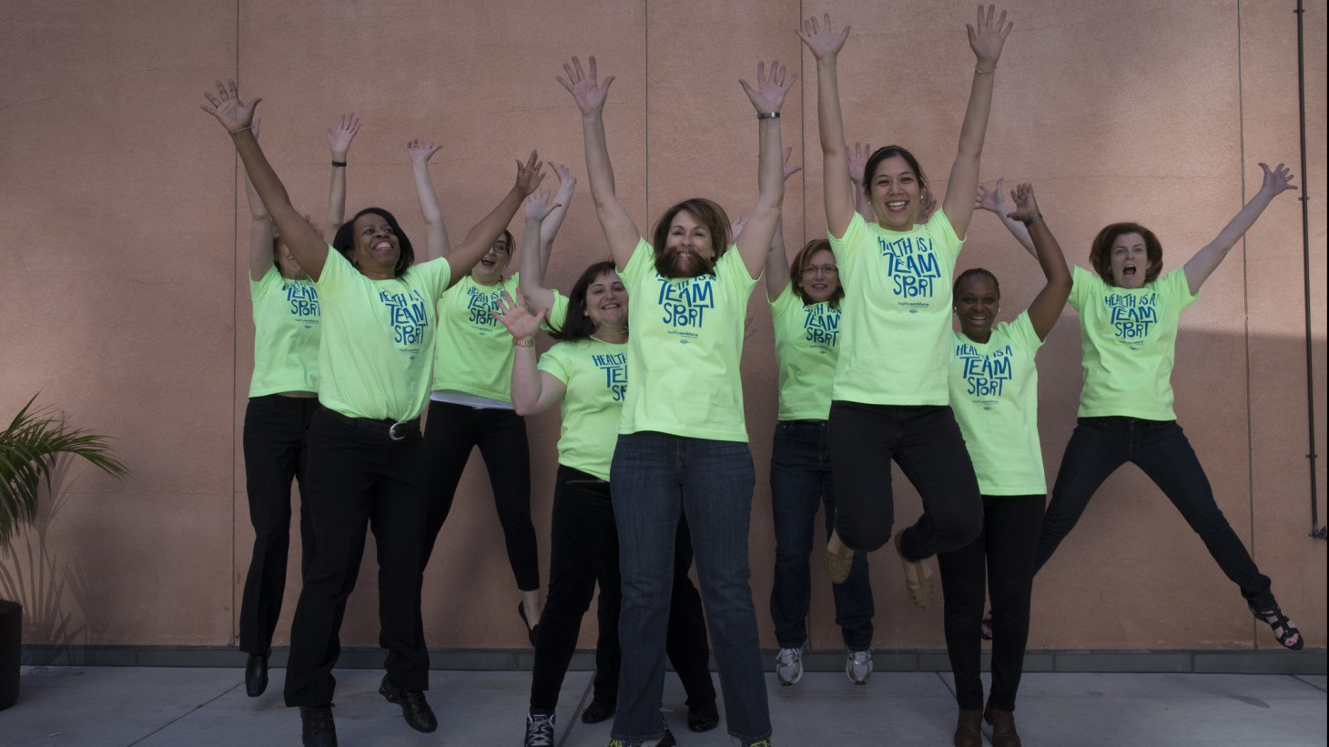 Squad of women in bright green shirts jumping up in the air