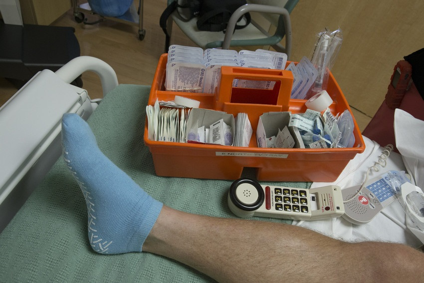 A foot wearing a blue non-slip sock with an orange tray of medical supplies next to it