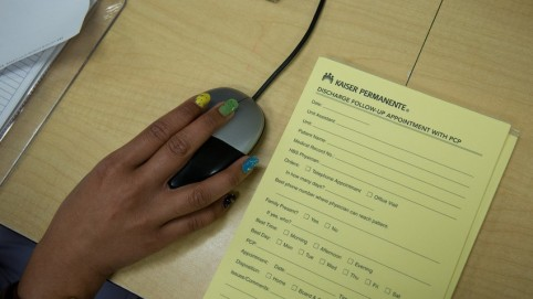 Yellow patient questionnaire and hand on a computer mouse