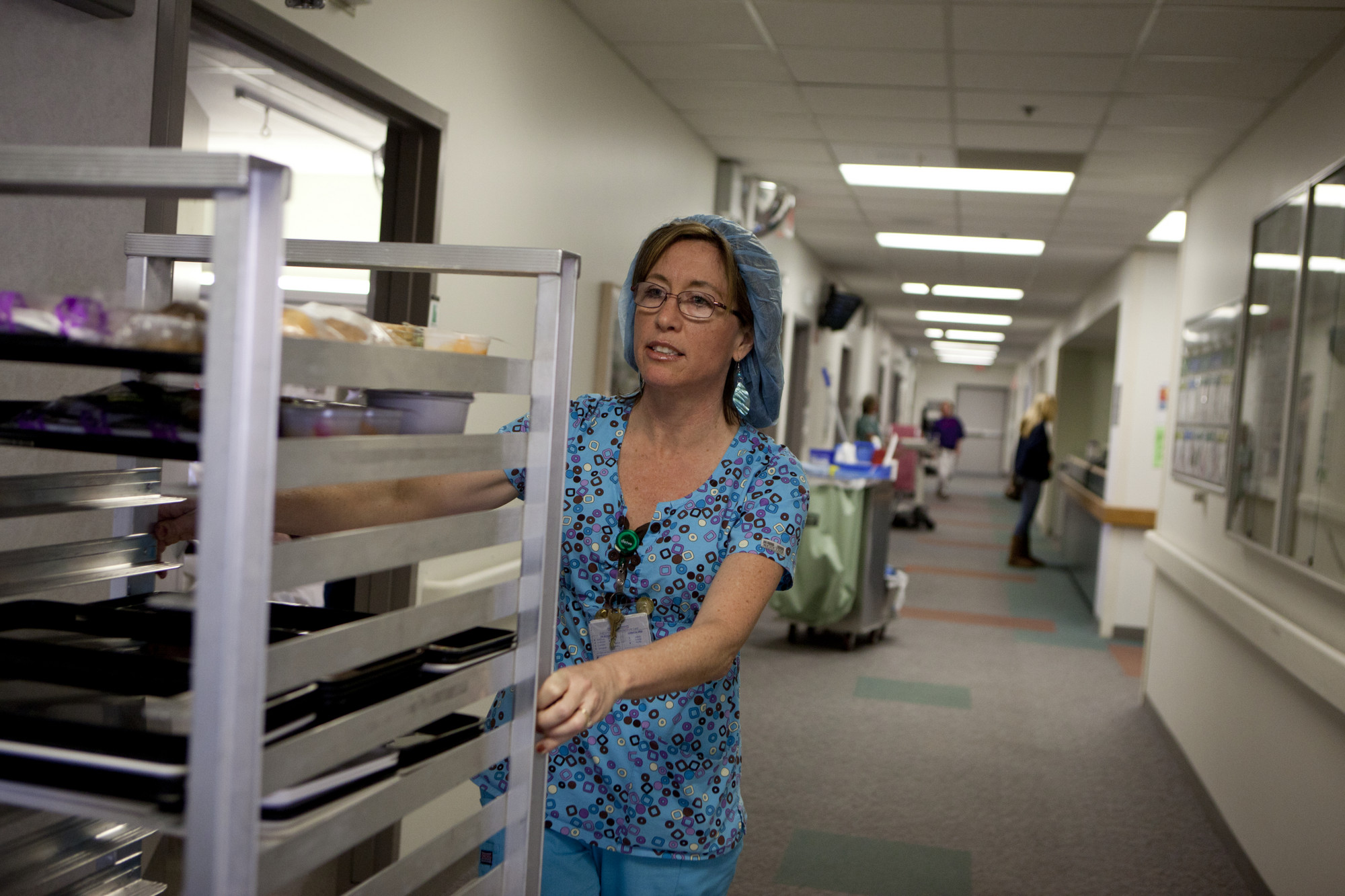 Nutrition aide pushing a cart of meals.