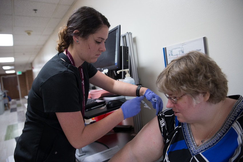 Nurse giving a female patient a flu shot