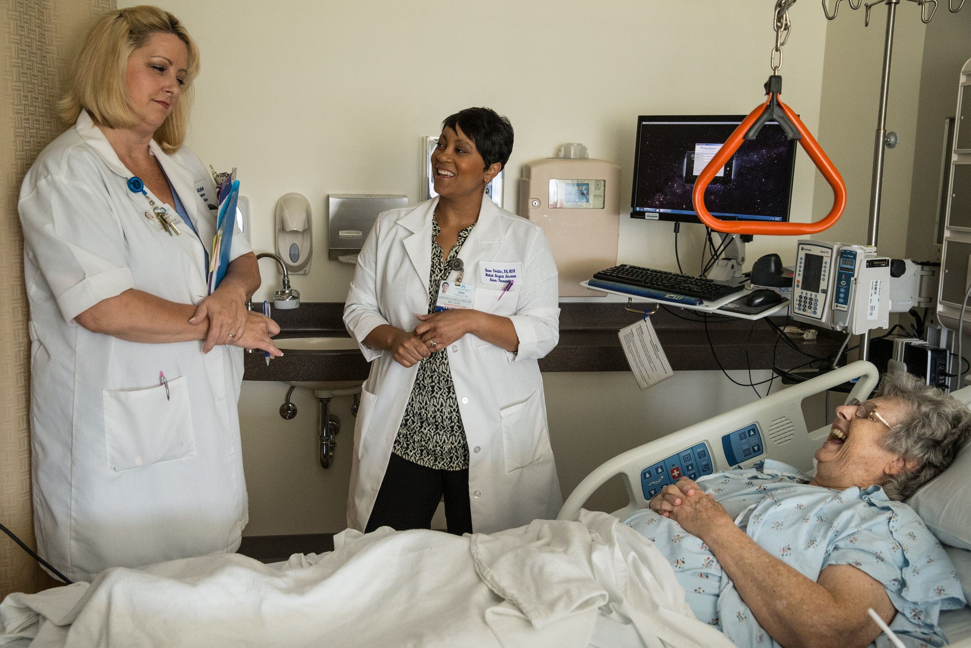 Two health care professionals in a hospital room with a patient