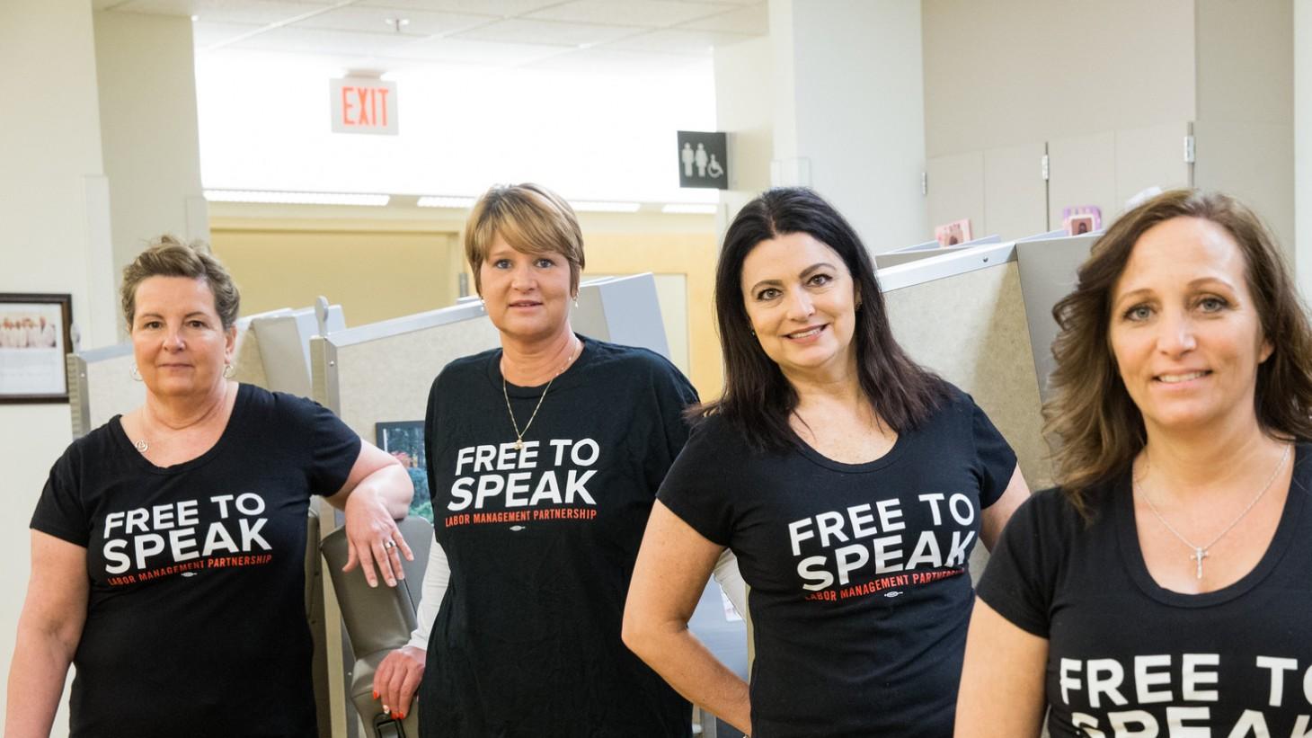 4 women wearing black Free to Speak t-shirts