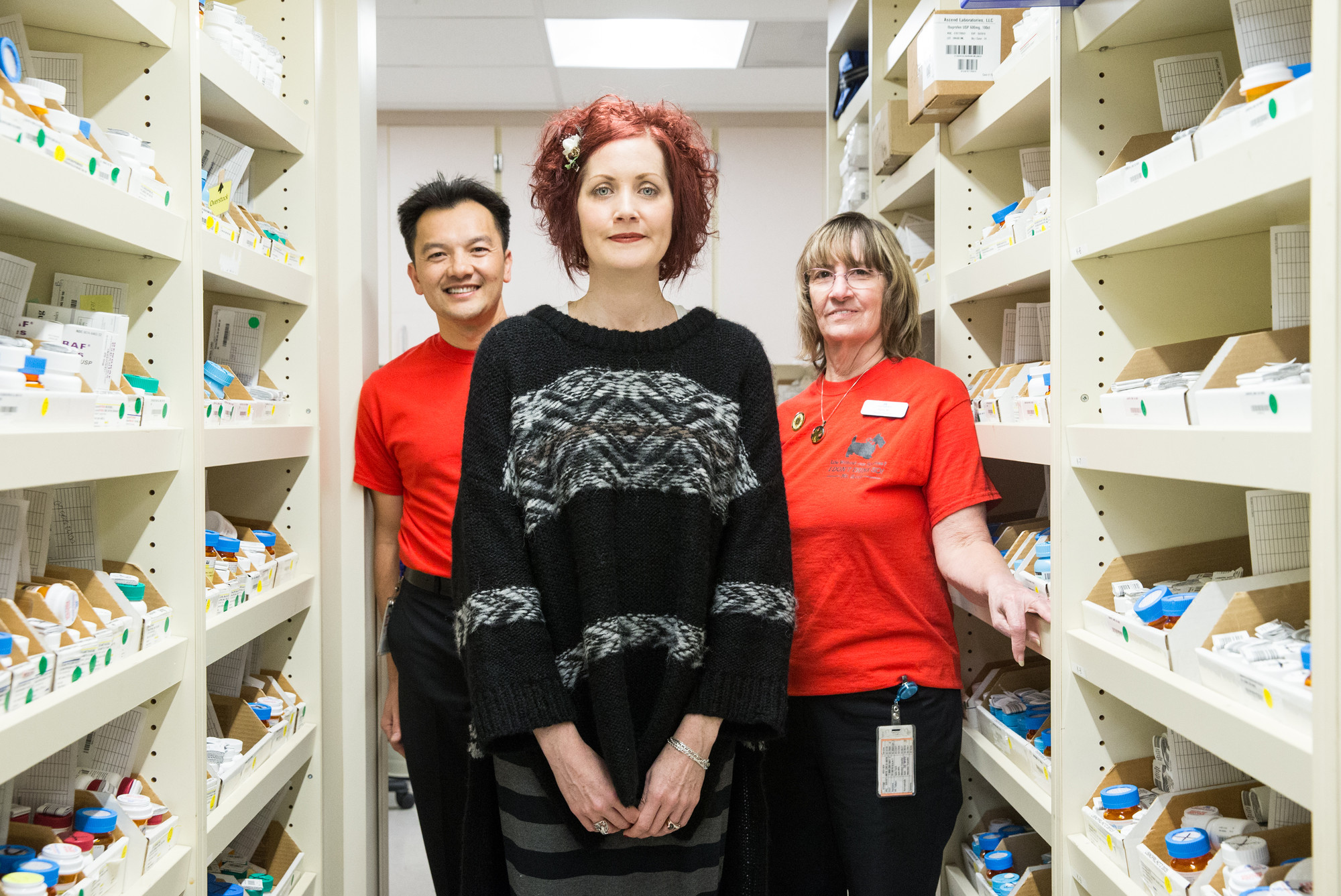 Three people standing amid shelves of pharmacy supplies