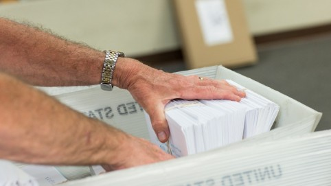 A man's hand in a tray of mail