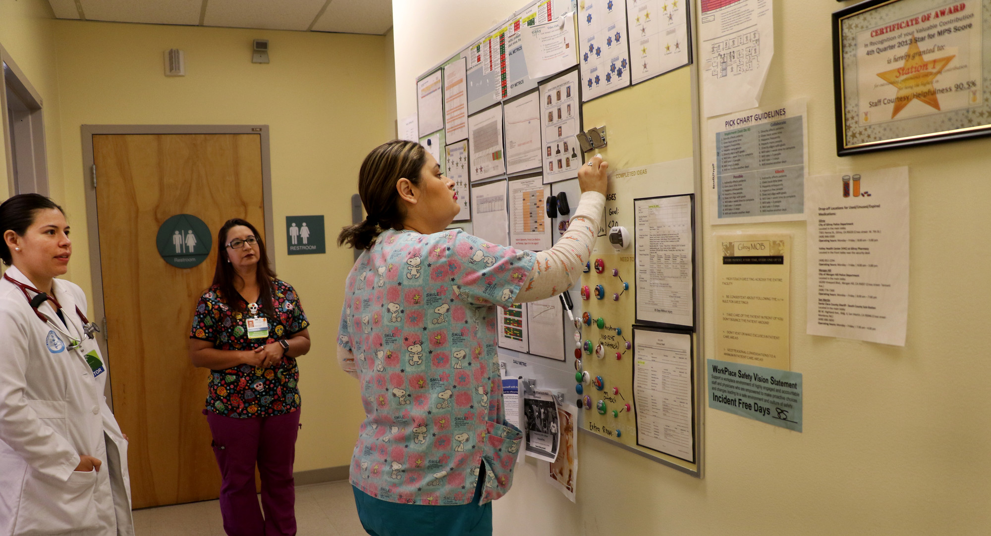 Health care workers filling in a huddle board in a clinic hallway
