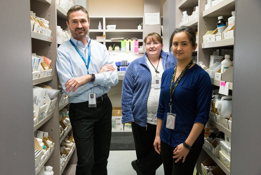 Three workers in a pharmacy supply room