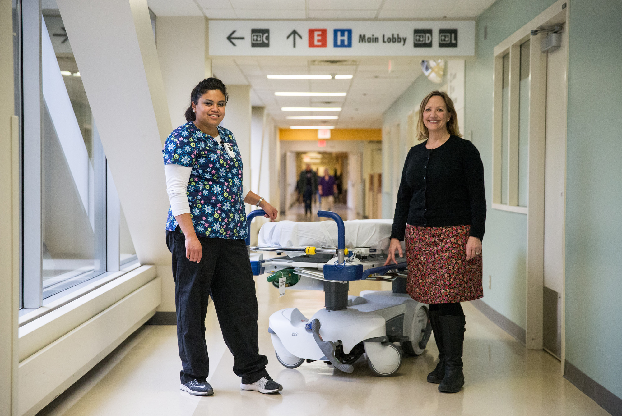 Esther Logan and Martha Witoe, standing next to a gurney in a hospital corridor.
