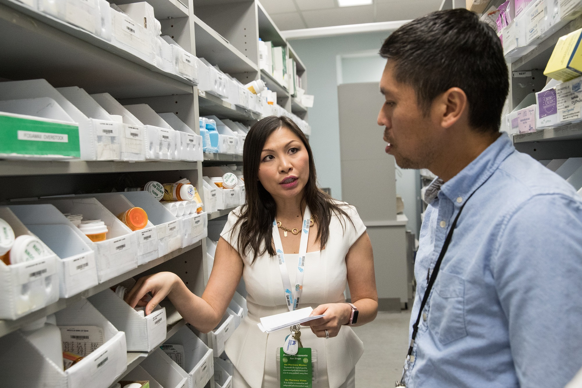 Two employees in a pharmacy supply room