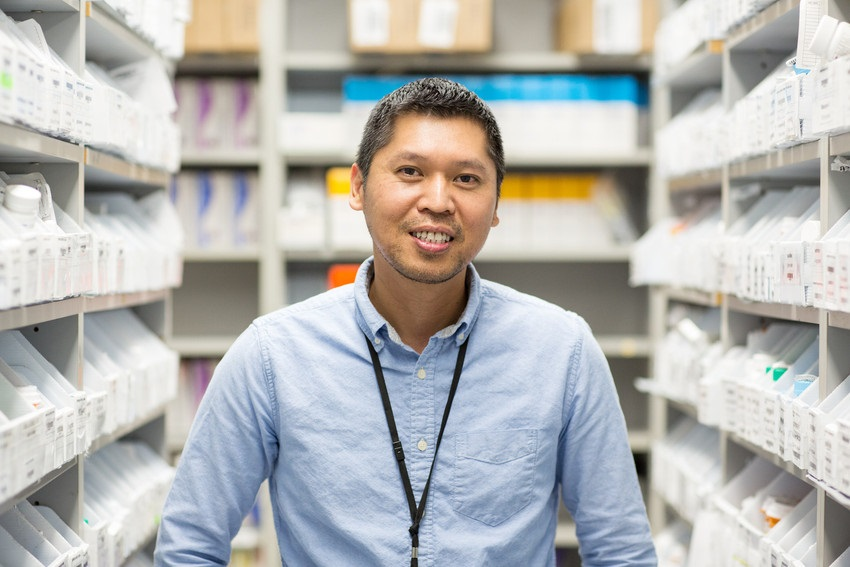 worker standing in a pharmacy stock room.