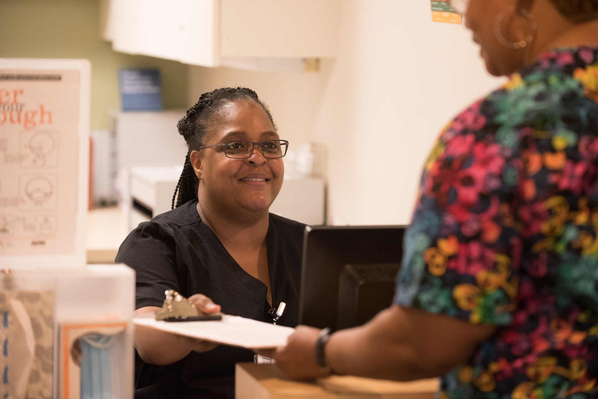 Receptionist checking in a patient for her appointment